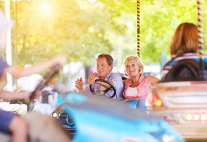 Senior couple having a ride in the bumper car at the fun fair