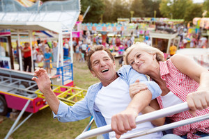 Senior couple having fun on a ride in amusement park. Summer vacation.