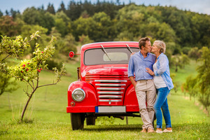 Senior couple hugging and kissing, vintage styled red car, green sunny nature