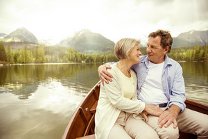 Senior couple hugging on boat on mountain tarn