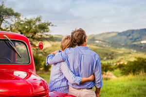 Senior couple hugging, vintage styled red car, green sunny nature, rear view