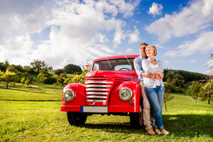 Senior couple hugging, vintage styled red car, green sunny nature