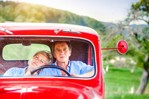 Senior couple in their vintage red car