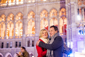 Senior couple in winter clothes on a walk in illuminated night city. Historical building. Vienna, Austria.