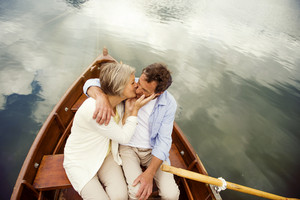 Senior couple kissing on boat on mountain tarn