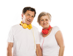Senior couple listening to music with headphones, isolated on white