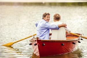 Senior couple paddling on boat on mountain tarn