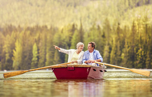 Senior couple paddling on boat with mountains in background