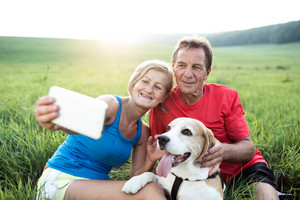 Senior couple running with their dog, resting, taking selfie with smart phone. Green sunny summer nature.