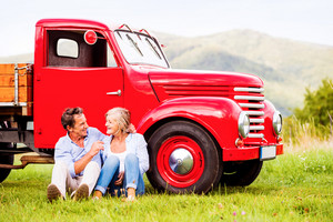 Senior couple sitting at the red vintage car, green sunny nature