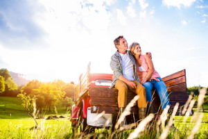 Senior couple sitting in back of vintage red pickup truck, hugging, green sunny nature
