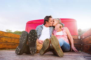 Senior couple sitting in back of vintage red pickup truck, kissing, hugging, sunny autumn day