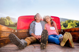 Senior couple sitting in back of vintage red pickup truck, resting, hugging, sunny autumn day