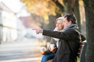 Senior couple sitting on bench, drinking coffee. Man pointing at something with his fingers. Sunny autumn nature.