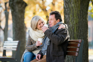Senior couple sitting on bench, drinking coffee. Sunny autumn nature.