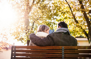 Senior couple sitting on bench, sunny autumn nature. Rear view