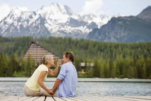 Senior couple sitting on pier above the mountain lake with mountains in background
