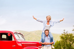 Senior couple standing at the red vintage car, green sunny nature