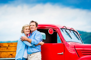 Senior couple standing by their vintage red car