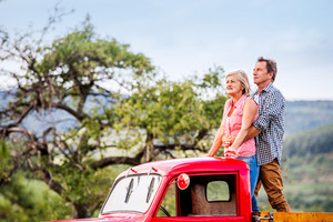 Senior couple standing in back of vintage red pickup truck, hugging, green sunny nature