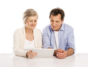 Senior couple using tablet, isolated on white background