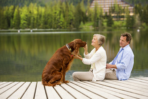 Senior couple with dog sitting on pier above the mountain lake with mountains in background