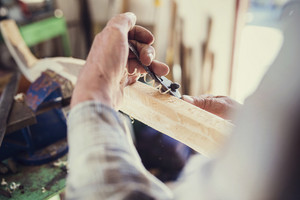 Senior craftsman working with planer on wooden pole in his workshop