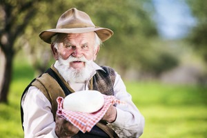 Senior farmer with organic cheese outside in green nature
