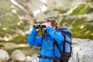 Senior hiker man enjoying the beautiful landscape view with binoculars during the hike