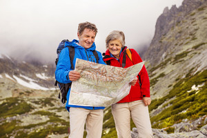 Senior hikers couple looking at the hike map during the hike in beautiful mountains
