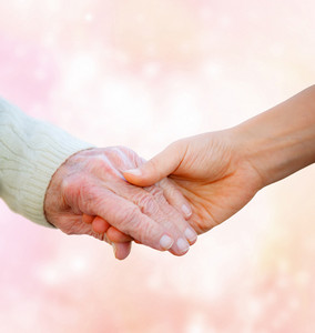 Senior Lady Holding Hands with Young Woman on Pink Lights Background