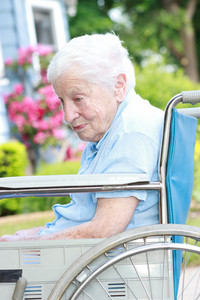 Senior lady in wheel chair in front of house with pink flowers