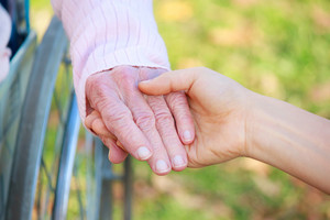 Senior Lady in Wheelchair Holding Hands with a Young Caretaker or Loved-one