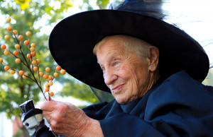 Senior lady in witch costume flying