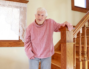 Senior lady smiling in front of staircase