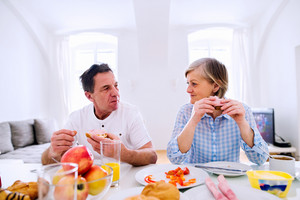 Senior man and woman having breakfast. Sunny morning. Table with food.