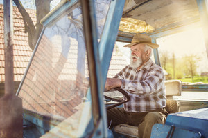 Senior man at the farm driving an old tractor