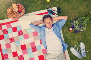 Senior man having a picnic lying on a colorful blanket