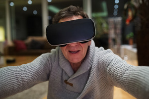 Senior man in gray sweater at home in his living room in the evening wearing virtual reality goggles, reaching out with his arm