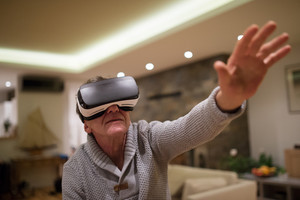Senior man in gray sweater at home in his living room in the evening wearing virtual reality goggles, reaching out with his arms