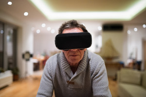 Senior man in gray sweater at home in his living room in the evening wearing virtual reality goggles