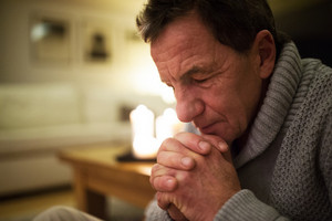 Senior man in gray sweater at home in his living room praying, hands clasped together, eyes closed. Burning candles behind him. Close up.