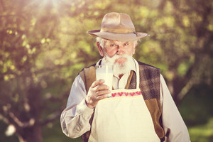 Senior man in orchard with glass of milk