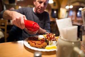 Senior man in restaurant puts ketchup on fries and vienna schnitzel