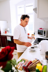 Senior man preparing coffee. Putting sugar in two white cups.