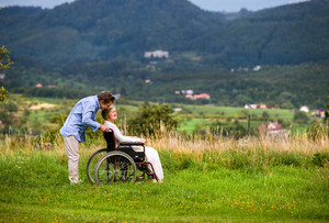 Senior man pushing woman sitting in wheelchair, kissing her, oustide in green autumn nature