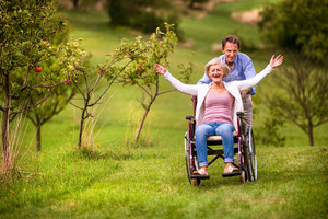 Senior man pushing woman sitting in wheelchair oustide in green autumn nature, laughing, arms stretched