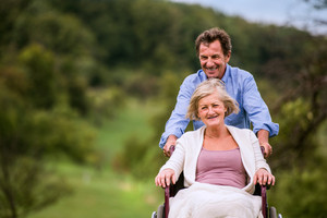 Senior man pushing woman sitting in wheelchair oustide in green autumn nature