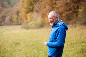 Senior runner in blue jacket resting outside in sunny autumn nature, laughing.