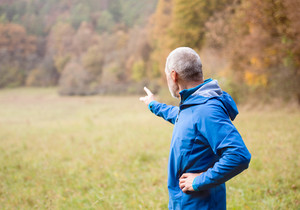 Senior runner in blue jacket resting outside in sunny autumn nature, pointing at something with his finger.
